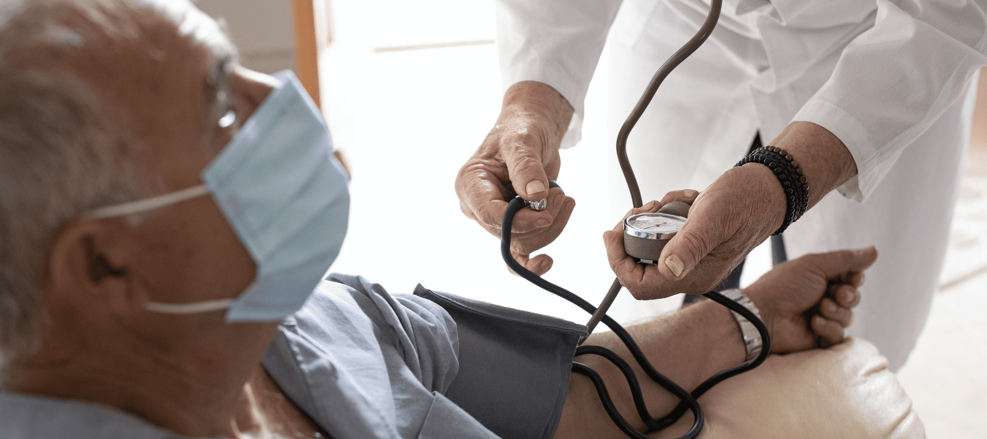 Physician taking masked patient's blood pressure
