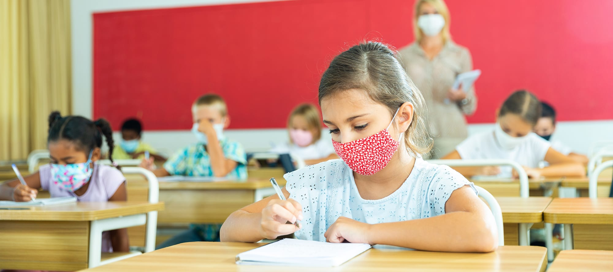 Child with medical mask sitting in classroom with classmates and teacher