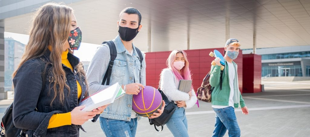 College Students walking together with medical masks on