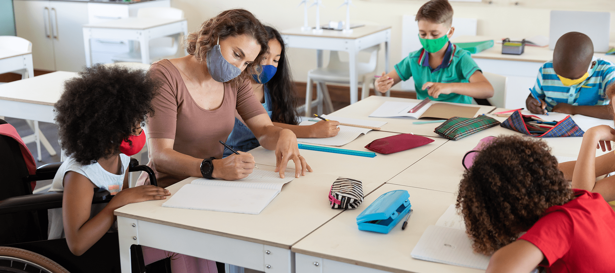 Teacher sitting at a table with students, all wearing masks.